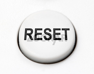 A white round button switch for reset close up. Control mechanical key for select idea of user on control device.
