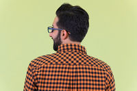 Closeup rear view of happy young bearded Persian hipster man smiling