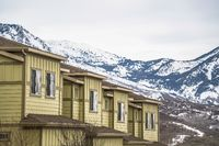 Row of cream colored homes with snow covered mountain and cloudy sky background