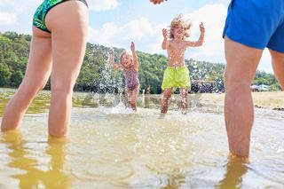 Kinder und Eltern spielen zusammen im Meer