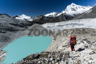 female mountain climber passes by a turquoise lake in the Andes in Peru