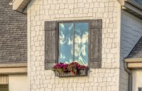 Rectangular window of a home with flower box and rustic wooden shutters