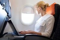Attractive caucasian female passenger looking through the plain window while working on modern laptop computer using wireless connection on board of commercial airplane flight