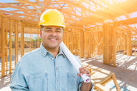Hispanic Male Contractor with Blueprint Plans Wearing Hard Hat At Construction Site