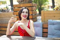 Woman wearing polka dots dress having wine in a restaurant