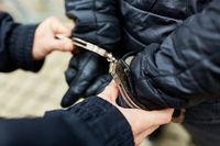 Polizist beim Abführen von Täter in Handschellen