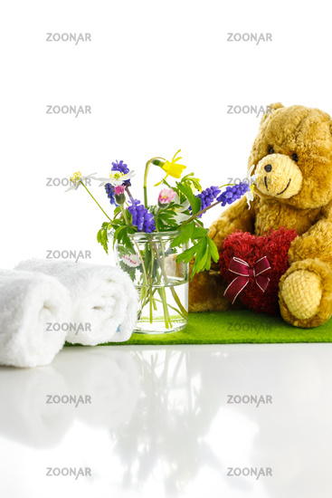 A teddy bear with a heart next to a vase of flowers and white towels. Spring is here.