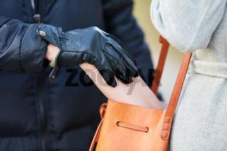 Dieb beim Stehlen von Brieftasche aus Handtasche