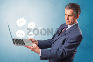 Man holding laptop with speech bubbles