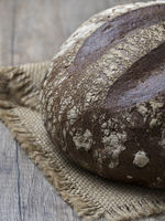 Round loaf of freshly backed sourdough bread on wooden background. Close up view.