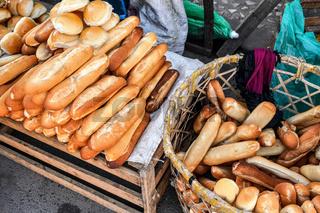 Fresh French baguettes and beads on morning market display at Fianarantsoa, Madagascar.