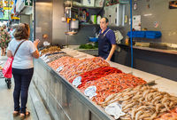Seller sells seafood in central market in Malaga, Spain