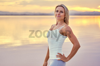 Woman in sportswear pose against cloudy bright sky at sunset