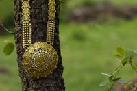 Artificial golden necklace on a nature background.