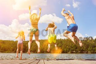 Familie springt in Wasser von See im Sommer