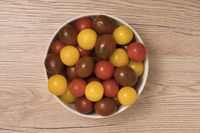 Cherry tomatoes, red,yellow and kamato in ceramic bowl on wooden background. Top view.