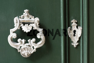 Vintage antiqued door knocker on wooden green door