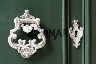 Vintage antiqued door knocker on wooden green door