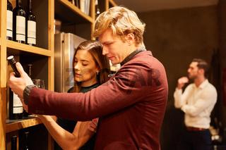 Junges Paar betrachtet eine Flasche Rotwein