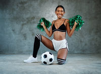 Portrait of beautiful young smiling girl with green cheerleader pom-poms and soccer ball