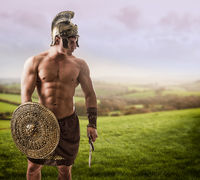Young muscular man posing in gladiator costume