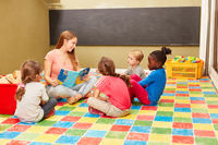 Gruppe Kinder und Lehrerin beim Vorlesen