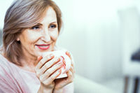 A Woman Over 50 Years of European Appearance Resting at Home Drinking Tea.