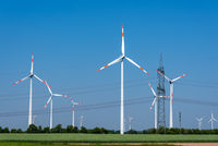 Overhead power lines and wind power plants under a blue sky in Germany