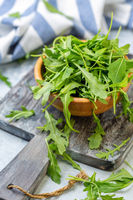 Arugula leaves in a wooden bowl.