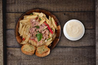 Pasta with tuna, garlic bread and parmesan cheese aside on rustic wooden background
