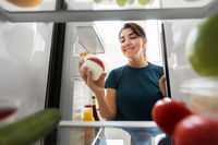 happy woman taking food from fridge at home