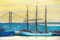 Ship by bridge at sunset