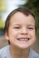 Outdoors closeup portrait of smiling freckled boy with dark hair and brown eyes