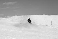 Skier downhill on snowy ski slope in sun winter day