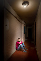 Sad and desperate woman sits in a dark corridor