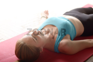 Young Caucasian woman laying in relaxing yoga pose on a mat in the class