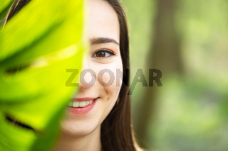 Beautiful natural young woman closeup behind big monstera leaf with green background in the woods.