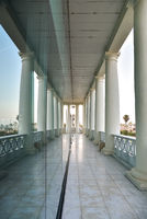 Exterior corridor overlooking the sea of a building with classic white columns reflected in a glass.