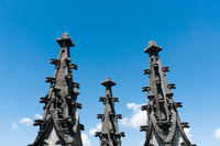the spires of the historic cathedral in Fribourg under a blue sky with white clouds