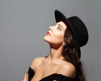 Profile portrait of a beautiful lady wearing a black hat and looks up