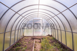 Greenhouse. Bright greenhouse in the garden. Indoor stationary greenhouse