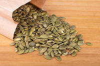 Peeled pumpkin seeds, in a paper bag, on wooden background