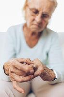 Heartbroken elderly woman holding he husbands wedding ring