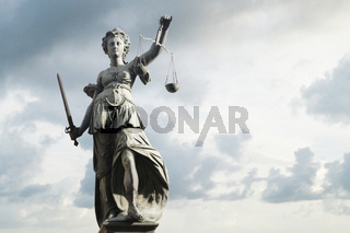 Justitia symbol of justice in front of background with sky and clouds