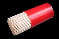 Wooden sharp toothpicks in red plastic container isolated on black macro