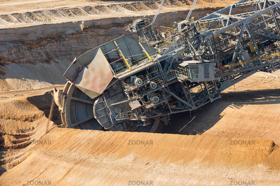 Brown coal open pit landscape with digging excavators in Germany