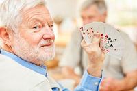 Senior zeigt seine Karten und hat Spaß