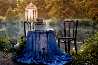 Romantic wedding dinner, in the Park by the water. Lots of green. Table for a romantic wedding dinner, date. The Park by the lake. In a blue color. With white bunk cake and serving for 2 persons.