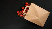 Top down view, brown paper shopping bag with cherry tomatoes laying on black marble like desk, space for text left down corner
