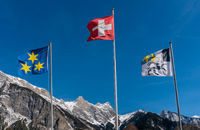 three flags waving in the wind in a mountain landscape in the Swiss Alps